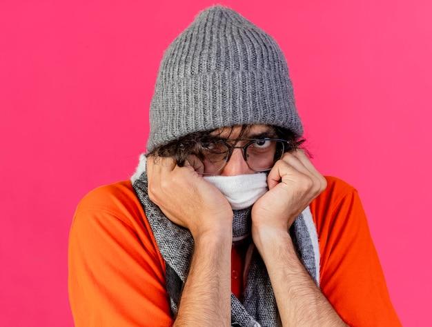 ピンクの壁に隔離された正面を見て、それに手を置くスカーフで口を覆っている眼鏡の冬の帽子とスカーフを身に着けている眉をひそめている若い病気の男の拡大図