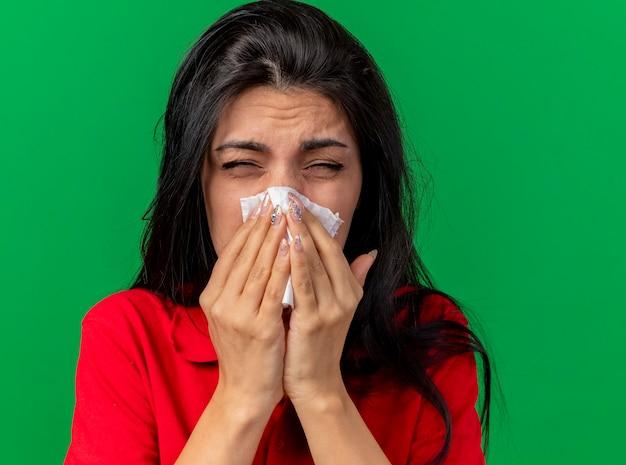 Крупным планом вид хмурящейся молодой больной женщины, вытирающей нос салфеткой с закрытыми глазами, изолированной на зеленой стене