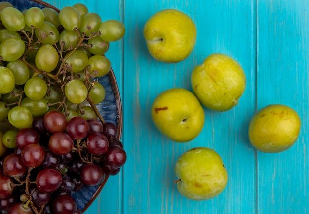 プレートのブドウとしての果物と青い背景の上の緑のプルオットのパターンの拡大図