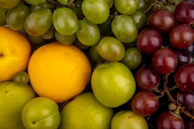 背景の使用のためのプルオットネクタコットプラムとブドウとしての果物の拡大図