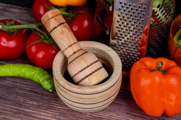 Взгляд конца-вверх дробилки чеснока с теркой и овощами как томат и перец на деревянном столе