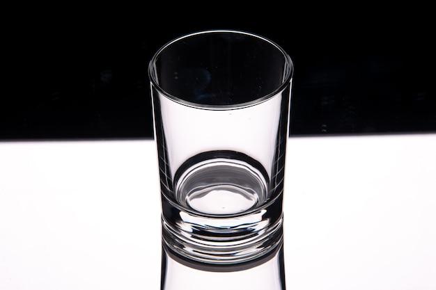 空きスペースのある暗い背景の上の白いテーブルの上のガラスカップのビューをクローズアップ