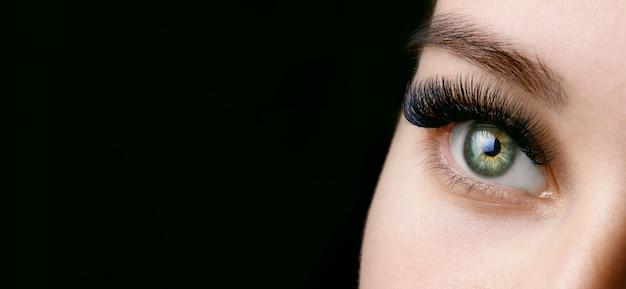 어두운 배경에 긴 속눈썹을 가진 녹색 여성 눈의 뷰를 닫습니다