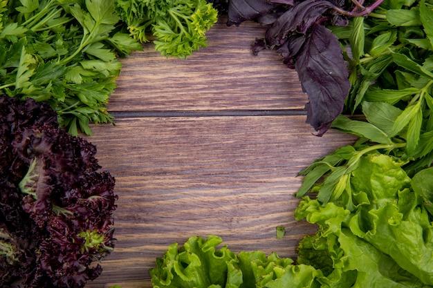 Взгляд конца-вверх зеленых овощей как базилик салата мяты кориандра на деревянном столе с космосом экземпляра