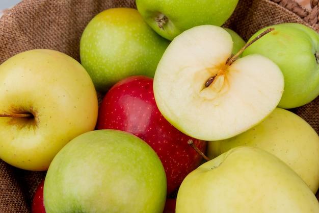 背景としてバスケットで緑黄色赤いリンゴのクローズアップビュー
