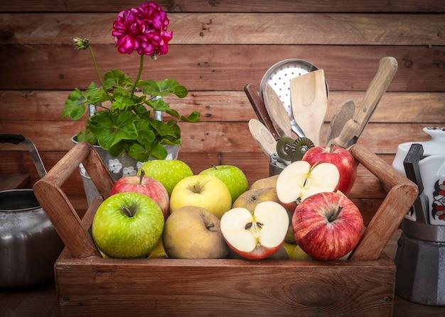 販売する準備ができている新鮮なリンゴのグループのクローズアップビュー。種類と色が異なります。木製のバスケットと素朴な背景。農民の収穫