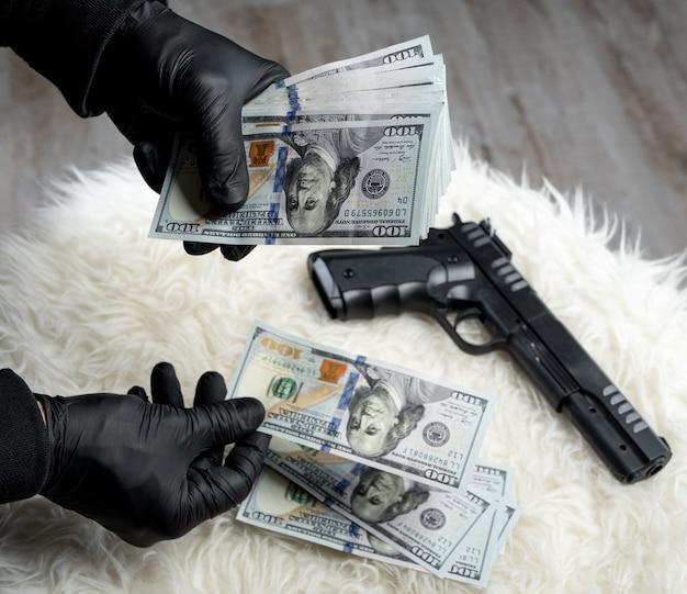 장갑을 낀 강도의 손에 있는 총과 달러의 클로즈업 보기