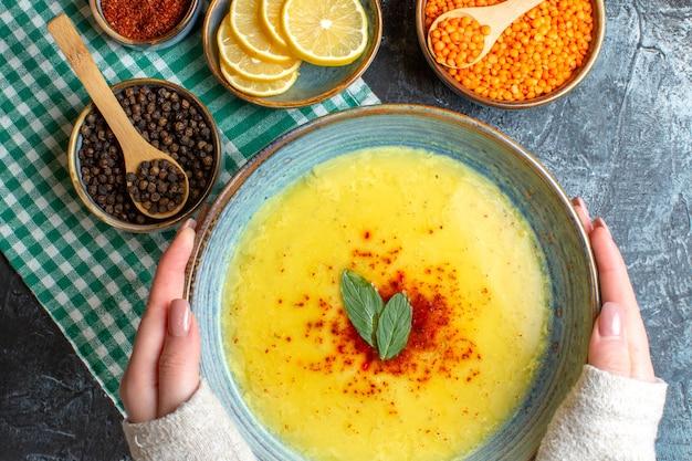 緑の皮をむいたタオルにミントとコショウを添えたおいしいスープが入った青い皿を持っている手の接写