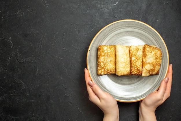 黒い背景の上の白いプレートにおいしい肉入りパンケーキを持っている手のビューをクローズアップ