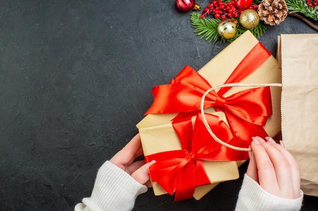 검은 배경에 가방에서 아름다운 선물 상자를 꺼내 손의 뷰를 닫습니다