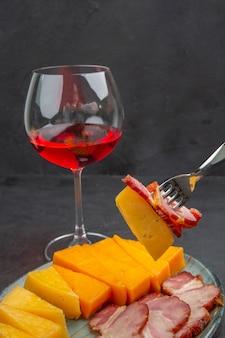 暗い背景に青い皿と赤いバラからおいしいソーセージとチーズのスライスをフォークで取った手のクローズアップビュー