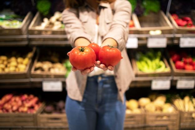 Крупным планом вид рук, держащих помидоры и овощи в супермаркете