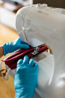 ミシンで布のフェイスマスクを縫う手のクローズアップビュー