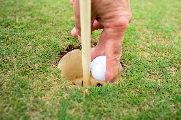 Крупным планом вид рук, вынимающих мяч для гольфа из лунки.