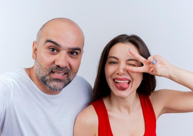 Крупным планом счастливая взрослая пара женщина, подмигивающая, показывает язык, делает знак мира, оба смотрят