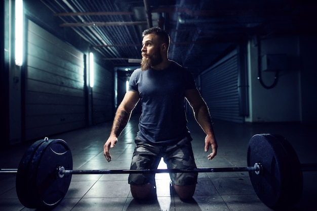 Крупным планом вид трудолюбивого, активного фитнеса, сильного бородатого культуриста, стоящего на коленях на полу, прежде чем поднять штангу в подземном гараже или городском тренажерном зале, глядя вдаль.