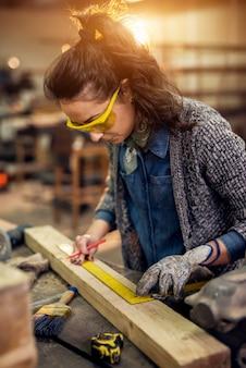 직물 작업장에서 테이블에 나무에 표시를하는 동안 근면 집중 전문 심각한 목수 여자 통치자와 연필을 들고의 뷰를 닫습니다.