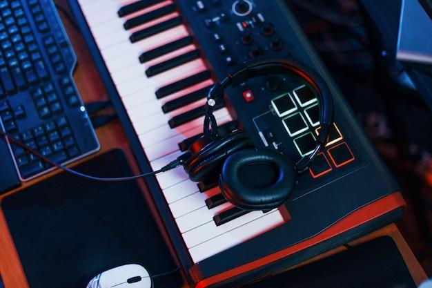 スタジオのキーボードに横になっているヘッドフォンのクローズアップビュー。