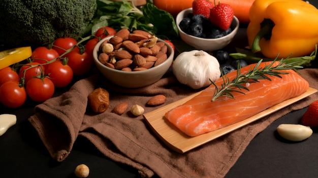 Крупным планом вид ассортимента здоровой пищи с лососем, фруктами, овощами, семенами и копией пространства на черном столе