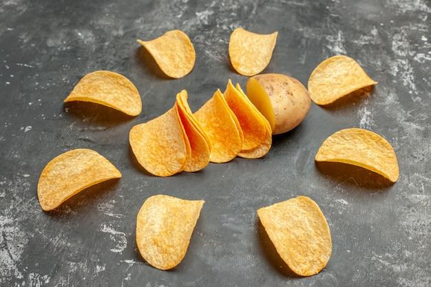회색 테이블에 집에서 만든 맛있는 감자 칩의 뷰를 닫습니다