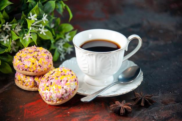 Крупным планом вид домашнего вкусного сахарного печенья и чашки кофейного цветочного горшка на фоне темных цветов со свободным пространством