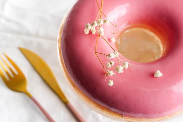 自家製フルーツピンクの艶をかけられたスフレフォークとナイフのクローズアップ表示は繊維の白い背景の上。