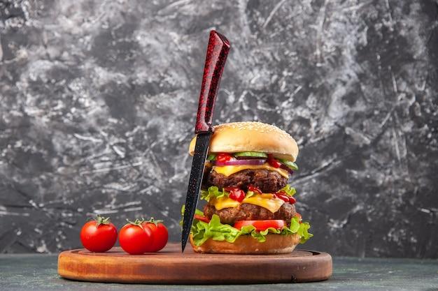 여유 공간이있는 어두운 색 표면에 나무 커팅 보드에 수제 샌드위치 토마토의 뷰를 닫습니다