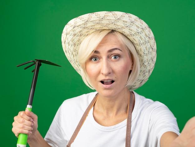 녹색 벽에 고립 된 손을 뻗어 괭이 갈퀴를 들고 모자를 쓰고 제복을 입은 감동적인 중년 금발 정원사 여자의 클로즈업 보기