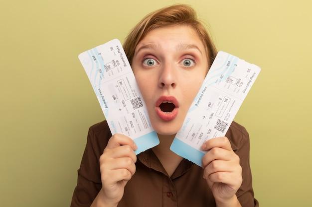 オリーブグリーンの壁に隔離された彼らと顔に触れる飛行機のチケットを保持している感動の若いブロンドの女の子の拡大図