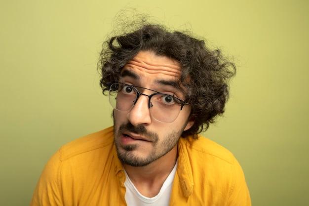 オリーブグリーンの壁に分離された正面の噛む唇を見ている眼鏡をかけている感動の若いハンサムな男のクローズアップビュー