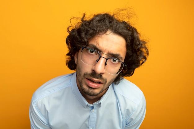 오렌지 벽에 고립 된 전면을보고 안경을 쓰고 감동적인 젊은 잘 생긴 남자의 근접 촬영보기