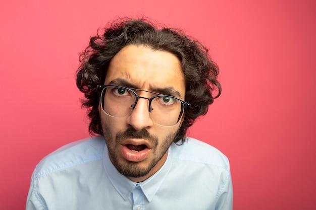 분홍색 벽에 고립 된 전면을보고 안경을 쓰고 감동적인 젊은 잘 생긴 남자의 근접 촬영보기