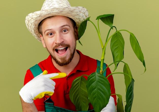 オリーブグリーンの壁に隔離された植物を保持し、指している庭師の手袋を身に着けている制服と帽子の印象的な若いハンサムなスラブ庭師の拡大図