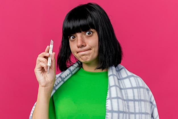 Крупным планом вид впечатленной молодой больной женщины, завернутой в плед, держащей термометр, смотрящей вперед, изолированной на розовой стене