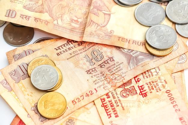 白い背景の上のインドの紙幣と硬貨のビューを閉じます。