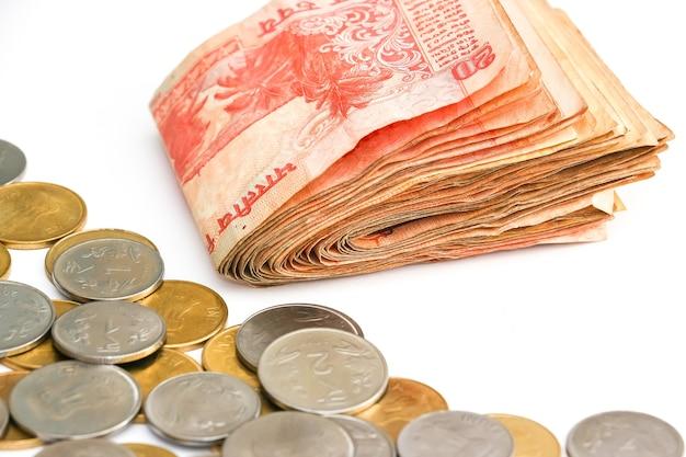 흰색 바탕에 인도 지폐와 동전의 보기를 닫습니다.