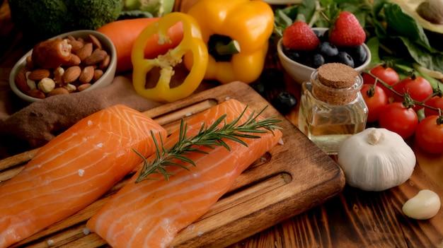 Крупным планом вид ингредиентов для здоровой пищи с лососем, фруктами, овощами и семенами на деревенском столе