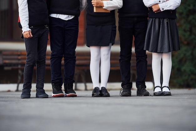교육 건물 근처에서 함께 야외에 있는 교복을 입은 아이들의 모습을 가까이서 보세요.