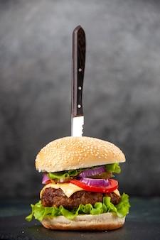 여유 공간이있는 고립 된 흐린 회색 표면에 검은 쟁반에 맛있는 샌드위치에 칼의 뷰를 닫습니다