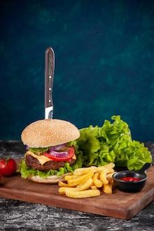 ダークブルーの表面に木の板にケチャップと茎唐辛子と肉のサンドイッチとフライド ポテト トマトのナイフのクローズ アップ