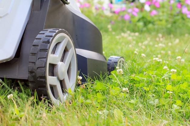 정원에 있는 푸른 잔디에 잔디 깎는 기계의 보기를 닫습니다. 잔디 깎는 기계. 정원사 관리 작업 도구를 깎습니다. 얕은 피사계 심도