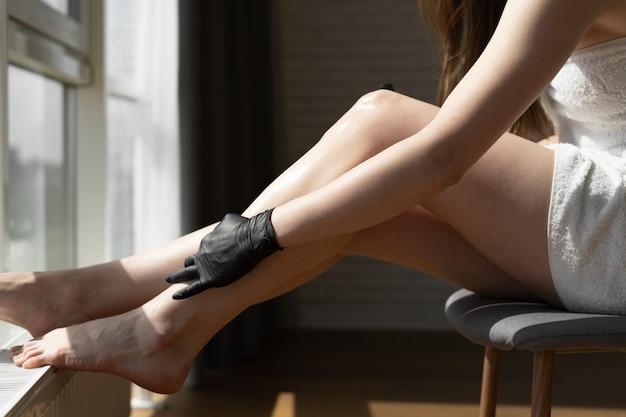 Крупным планом вид ног молодой кавказской женщины, сидящей на стуле перед окном спальни. концепция женской красоты