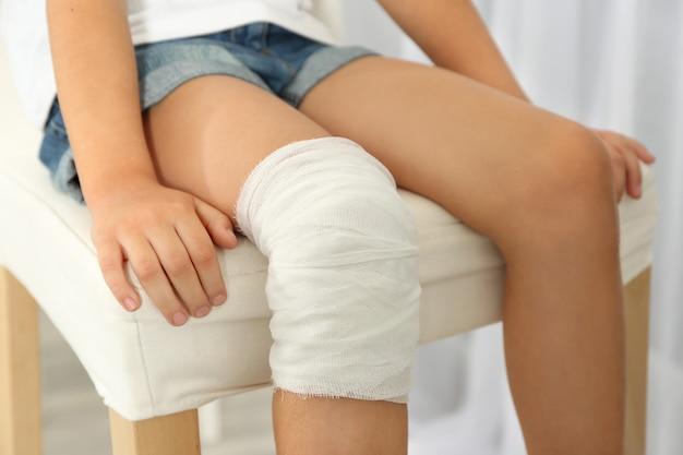 붕대로 어린 소녀의 무릎을 볼을 닫습니다