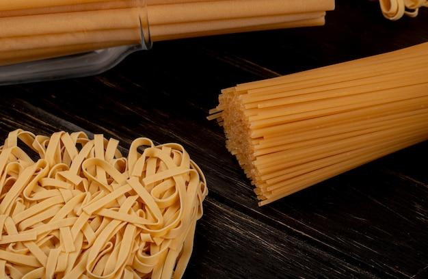 木製のテーブルにタリアテッレブカティーニスパゲッティとしてmacaronisのクローズアップビュー