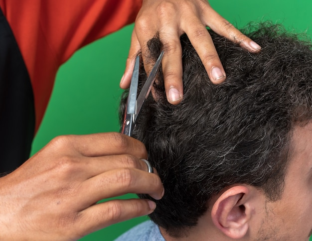 彼の若いクライアントのために散髪をしている男性の床屋の手のクローズアップビュー