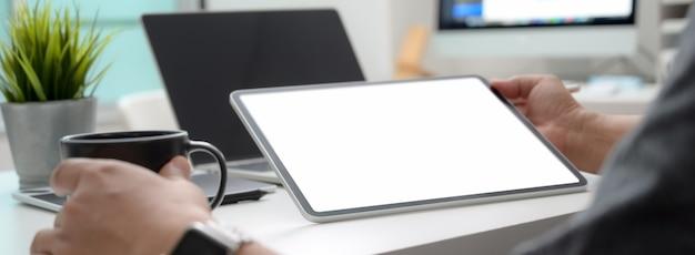 빈 화면 태블릿에 정보를보고 커피를 마시는 남성 기업가의 뷰를 닫습니다