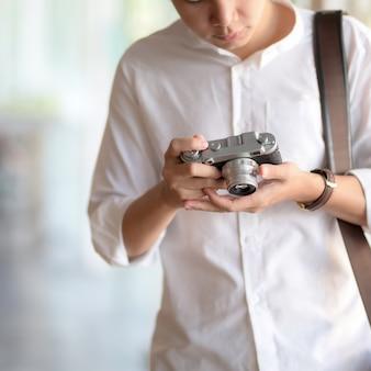 デジタルカメラで写真をチェックする男性カメラマンのクローズアップ表示