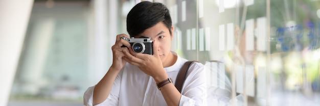 男性カメラマンがデジタルカメラで写真を撮影のクローズアップ表示