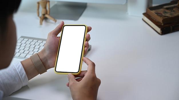흰색 책상에 빈 화면이 스마트 폰을 모의 들고 남자 손의보기를 닫습니다.