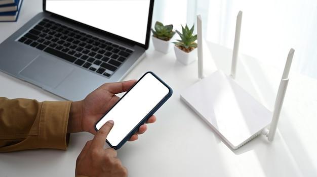 Крупным планом вид человека, использующего мобильный телефон для подключения к беспроводной сети дома.